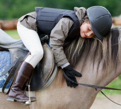 Kind auf Pferd mit Sicherheitsausrüstung